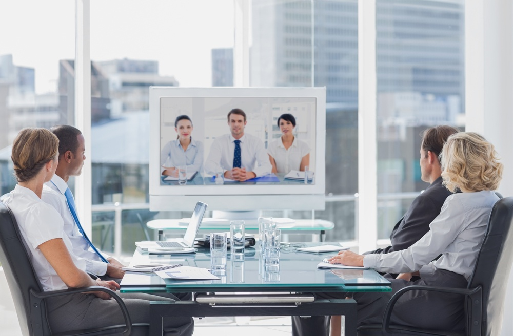 Business team having video conference with another business team in office.jpeg
