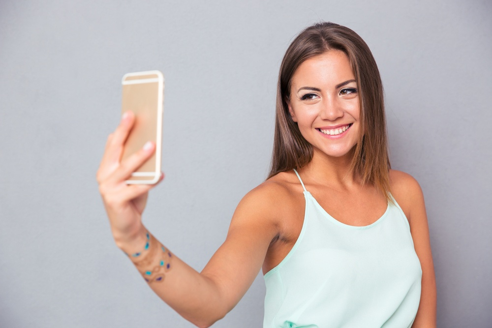 Smiling young girl making selfie photo on smartphone over gray background.jpeg